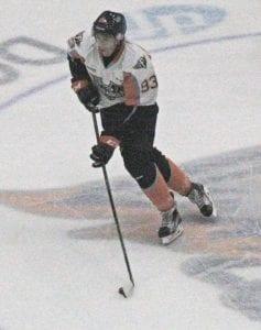 Flint's Hunter Holmes skates the puck across center ice.