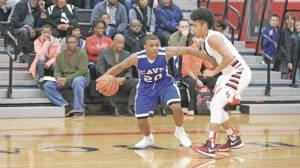Ja'Kavien Lewis tries to dribble around a Grand Blanc defender during Tuesday's game.