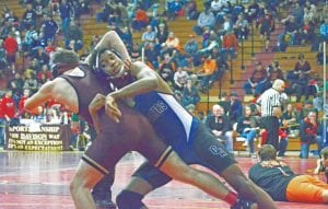 Carman-Ainsworth's Kenyon Jackson tosses an opponent at 140 pounds at the Genesee County Meet at Davison on Saturday.