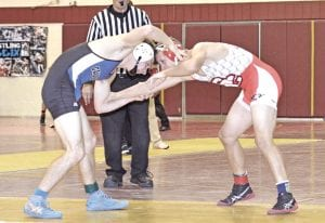 Nathan Delong of Carman Ainsworth grapples with a Swartz Creek opponent on Dec. 17.