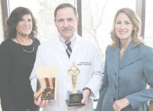 J. Wesley Mesko, MD, Michigan Orthopedic Center, center, proudly displays the national Best of Show creative award and winning brochure created by Publicom's team including Laura Dixon, vice president creative director, at left, and Lisa O'Connor, president.