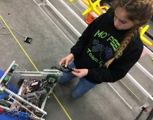 Lydia Minzey, 12, uses a protractor to measure how far the robot has turned, during an Open House last weekend, showcasing the robotics teams' preparation for the World competition in mid- April.