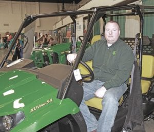 Sean Borton, a sales representative from Tri County Equipment in Burton, posed for a photo on the company's John Deere Gator XUV560, a crossover utility vehicle sold at Tri County. Borton said that he and the Tri County Equipment team help their customers tackle all the tough jobs around their property, and were able to offer expert home and garden improvement advice to attendees at the Home & Garden Show.