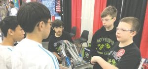 (right to left): Parker Oosterhof, 12, Alex Wickham, 13, and Adrien Fragoso, 12, talking strategy with their alliance partner from China prior to one of the qualifying matches.