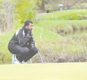 Carman-Ainsworth's Tyson Fields reads his putt during Monday's Jamboree at Davison.