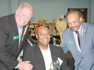 The Food Bank of Eastern Michigan's President, William Kerr (left) and the chair of the Food Bank's board, Claude High (far right) presented Mel Newhouse (center) with the Edward A. Mitchell Million Pound Club Award at the Food Bank's Annual Meeting last Wednesday evening at their Hunger Solution Center.