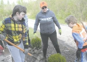 Youth volunteers helped clean up the swings area and put down wood safety chips. Youth and parents planted evergreen shrubs. Members of the Gleaner Arbor, which spearheads the annual clean-up, include (left to right) Patricia Wood, Margaret O'Sullivan, Millie Wint, and Peter Mikelens.