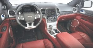 The driver-focused interior of the 2018 Jeep Grand Cherokee Trackhawk features premium soft-touch materials, unique Light Black Chrome finishes and carbon fiber spears, and a 7-inch driver information display (DID) instrument cluster, which features the tachometer in the middle. The 200-mph speedometer is on the left side of the cluster.