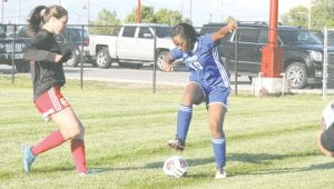 Carman-Ainsworth's Aja Williams uses her footwork to get past a Swartz Creek opponent during the district opener.