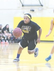 Carman-Ainsworth's Ayanna Watkins dribbles up court for the Black squad in the annual Bruin Classic girls' basketball game at Ballanger Field House last Thursday.