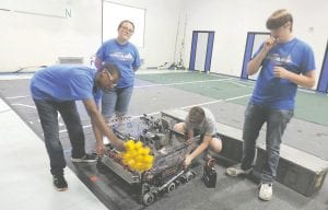 Byzjon Speights, Katie McGilvery and Jacob White (left to right in the blue shirts) were among team members in the gym putting three seasons of robots through their paces.