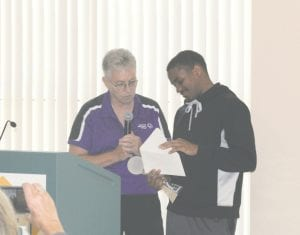 Special Olympian Dalvin Keller opens a letter after receiving his honorary ESPY, accompanied by volleyball coach Sheila Gafney, during a ceremony at the GISD Transition Center on Monday.