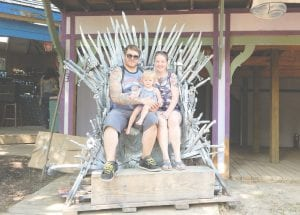 [L-R] Bobby Cantrell, Layla Cantrell and Krystal Walker of Monroe sit in the new iron throne, modeled after the one popularized by HBO's Game of Thrones.