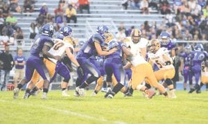 Carman-Ainsworth's quarterback, Dustin Fletcher, looks for an opening during a game with Davison last season.