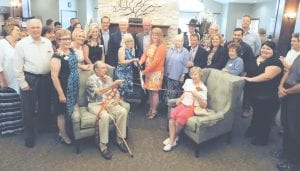 Surrounded by staff, management and owners, as well as city officials and members of the Swartz Creek Area Chamber of Commerce, Glen and Roberta Tuck hold the ribbon for the official ribbon-cutting ceremony at Springvale Assisted Living in Swartz Creek.
