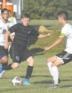 Carman-Ainsworth's Eli Young looks to escape two enclosing Flushing opponents during the game on Aug. 23.