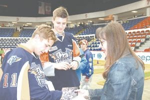 Cathy Bateson, of Grand Blanc, got a quick autograph from #11 Dennis Busby, a defenseman for the Firebirds, as fellow defenseman #3 Nikita Alexandrov looked on.