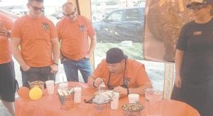 Philip Howell of Burton Fire Station 1 indulges in tasty Texas Roadhouse ribs as the first contestant at the 3 p.m. contest. Flint Township fire fighters and police officers also participated.