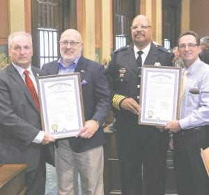 State Rep. Phil Phelps (D-Flushing) is joined by state Rep. Joseph Graves (R-Linden) to present a special tribute to Bishop International Airport Department of Public Safety police officer Lt. Jeff Neville, Chief of Public Safety Christopher Miller and Airport Maintainer Richard Krul on the House floor at the state Capitol in Lansing on Thursday, Sept. 14.