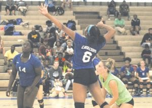 Carman-Ainsworth's Diamond Lester (6) rises up for a spike, while Amaya Campbell, left, and Morgan Sherrer, right, look to make a play on September 12.