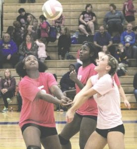 Carman-Ainsworth's Destiny Johnson, left, and Morgan Sherrer, far right, try to keep the point alive, as teammate Anita Harmon, center, keeps an eye on the ball on October 12.