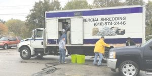April Paylor, owner of AJP Commercial Shredding, busily shreds residents' documents as Mark and Paul Nebraski work to unload material.