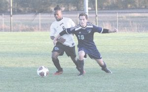 Carman-Ainsworth's Alex Williams tries to get around a Lapeer opponent in the district opener on Oct. 17.