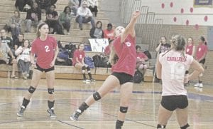 Carman-Ainsworth's Katie Speaks follows through on a dig, while Hannah Thurston (2) and Morgan Sherrer sit ready for action on October 12.