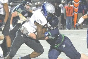 Carman-Ainsworth's Jacari Roberts fights through a tackle during a game with Lapeer on October 20.