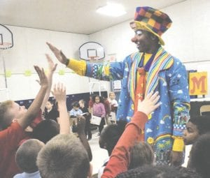 "Peanut (Eli Wilson) of The Mott Campus Clowns, high-fiving Grand Blanc Academy students at the end of the anti-bullying show, ""Turning Frowns Upside Down One Smile at a Time."""