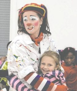 "Tinkers (Alyshia Turner) and Grand Blanc Academy student Serenity Teed share the last hug of the day at The Mott Campus Clowns anti-bullying show, ""Turning Frowns Upside Down One Smile at a Time."""