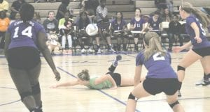Carman-Ainsworth's Morgan Sherrer lays out to keep the point alive, as Amaya Campbell (14) Hannah Thurston (2) and Katie Speaks (5) stand by ready for action.