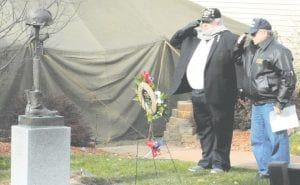 Vietnam War combat veterans Joseph M. Mishler and Don Austin place a wreath at the base of the fallen soldier battle cross at Veterans Memorial Park in Gaines.
