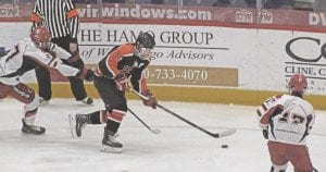 SCF's Kamryn Houle skates the puck up the boards against Grand Blanc last season.