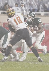 Carman-Ainsworth grad and Michigan State University fifth-year senior Gerald Holmes (24) tucks and rushes against Maryland in State's final home game of the season Saturday in East Lansing.