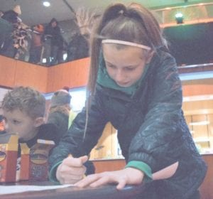 Fiona Betzold, 11, coloring holiday pictures at The Whiting.