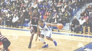 Carman-Ainsworth's Ja'Kavien Lewis takes a Grand Blanc defender baseline on Dec. 5.