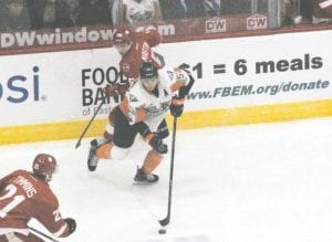 Flint's Ty Dellandrea looks for the pass as he skates the puck between a pair of Sault Ste. Marie defenders.