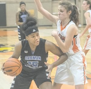 Carman-Ainsworth's Arie Lewis forces her way to the basket against Flushing on Nov. 28.
