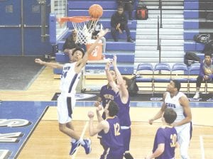 Carman-Ainsworth's Chris Ballard tries to rise above the rim for a rebound against Bay City Central on Jan. 16.
