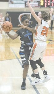 Carman-Ainsworth's Jessiana Aaron passes the ball under the basket against Flushing on Nov. 28.