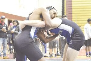 Carman-Ainsworth's Mykah Lewis, left, grapples against teammate Nathan Delong at the County Meet on Dec. 16.