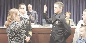 Surrounded by his wife, children and mother, newly promoted Captain Jason McClanahan was sworn in by Clerk Kathy Funk at the township board meeting Monday night.