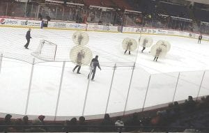 Credit union employees battle it out during a friendly game of bubble ball on the ice at Dort Federal Credit Union Event Center.