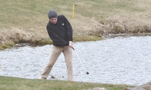 Carman-Ainsworth's Aaron Carter chips out of the rough during a meet at Metamora Golf and Country Club on April 25.