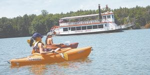 Paddlers enjoy some time on Mott Lake with the Genesee Belle traveling the waters behind them. The Genesee Belle departs from Crossroads Village. Mott Lake is a body of water made possible as part of the original Master Plan for the parks in the city of Flint. It was created by damming a section of the Flint River.