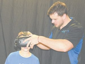 Brandon Fitch, 11, of Burton, gets a hand from Adam Sally, of Escape VR, while testing out the company's virtual reality headset. The VR booth was one of the biggest draws at Robo-Con this year.