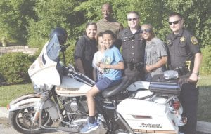 Residents posing with Genesee County Sheriff Department officers
