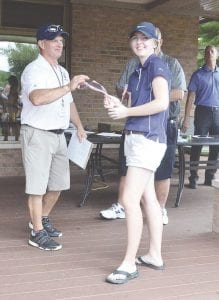 Goodrich's Elizabeth Gibbs accepts her top- 10 medal from Lapeer coach Steve Carlson at last Friday's Tune-Up. Gibbs finished second individually with an 81. Photo by Austin VanDaele