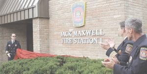 Flint Township Fire Chief Thomas Stadler, left, removed the covering from the sign dedicating Fire Station No. 1 to the late Chief Jack Maxwell, at a ceremony Aug. 16. Photo by Gary Gould